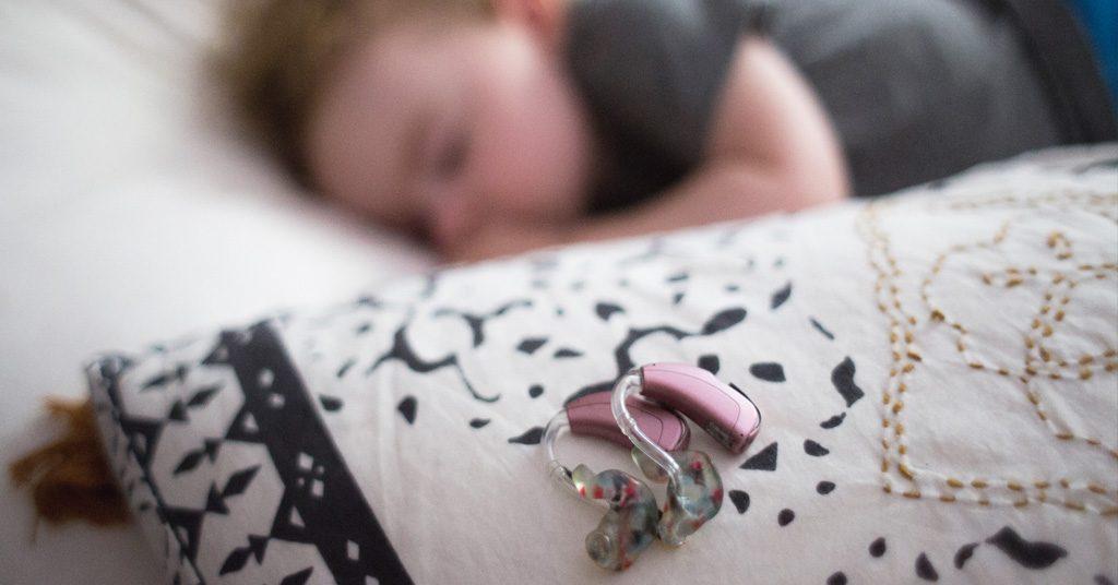 Bebé durmiendo en el fondo y audífonos phonak en la almohada junto a él