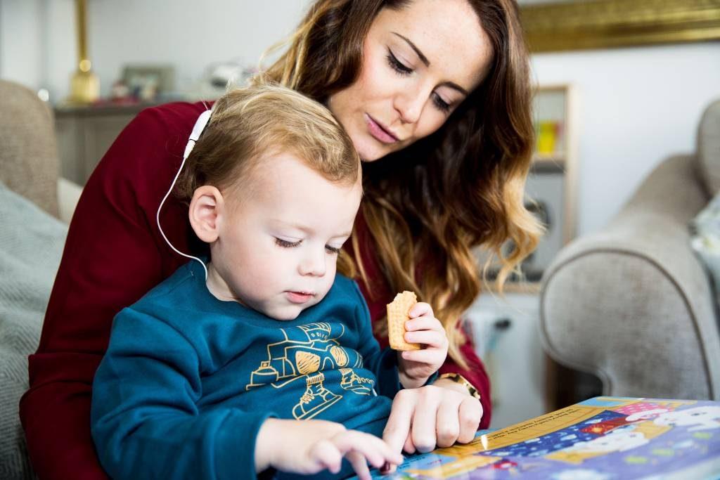 Niño con implante coclear sentado en el libro de lectura del regazo de la mujer