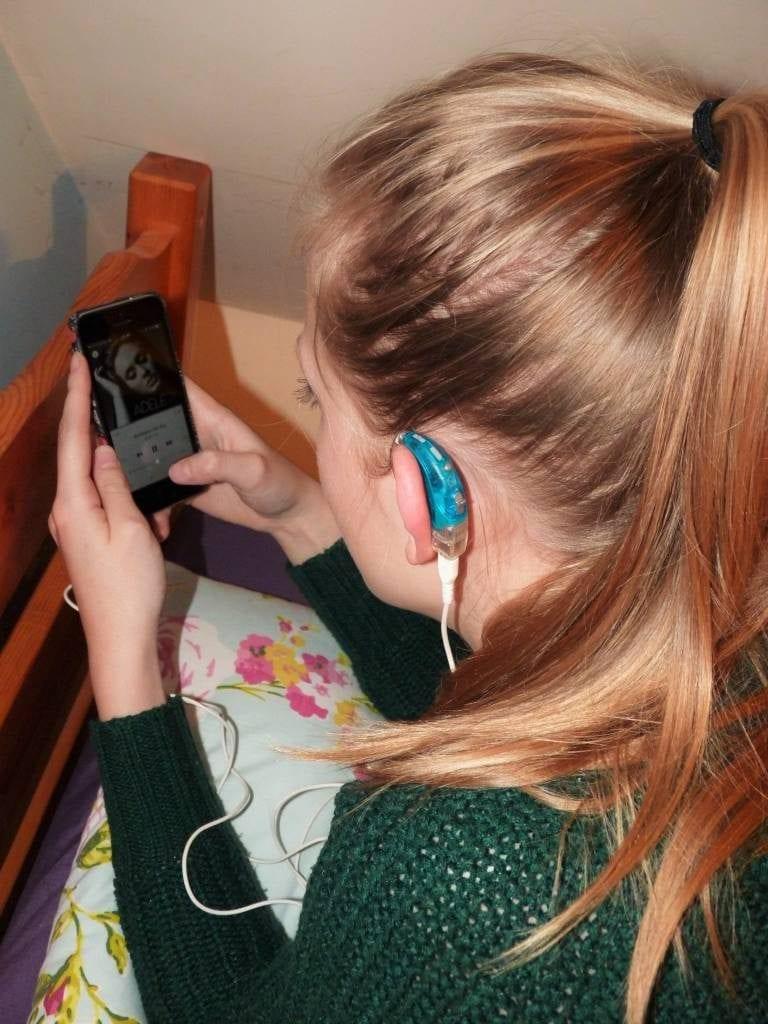 Chica con pérdida auditiva escuchando a Adele en su dispositivo