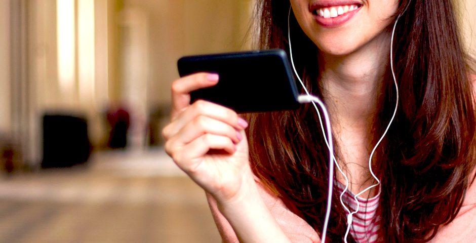 Chica escuchando música con auriculares y sonriendo