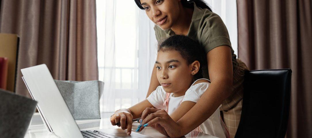 Mujer adulta ayudando a una niña a escribir en la computadora en la sala de casa.