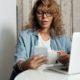 Mulher de cabelo cor caramelo está usando um óculos preto, segurando uma xícara na mão esquerda e segurando um celular na mão direita. Seus olhos estão na direção do celular. Ela está sentada em frente de um notebook, que está em cima da mesa e atras dela está uma geladeira.