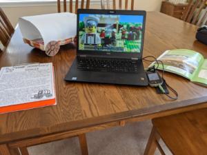 Computadora negra sobre una mesa de madera, en la pantalla con la transmisión de un diseño lego. También hay una revista y un portapapeles sobre la mesa. Conectado a la computadora está el micrófono con pantalla táctil Phonak Roger.