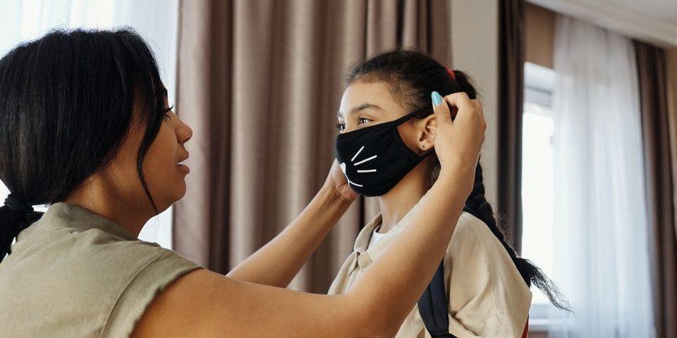 Mujer poniéndose una mascarilla negra con un dibujo que se asemeja a la cara de un gato en una niña, que lleva una mochila a la espalda.