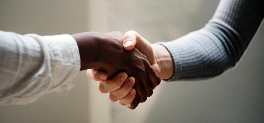 Dos manos dándose la mano o dándose la mano. Uno con un tinte blanco y el otro con un tinte negro.