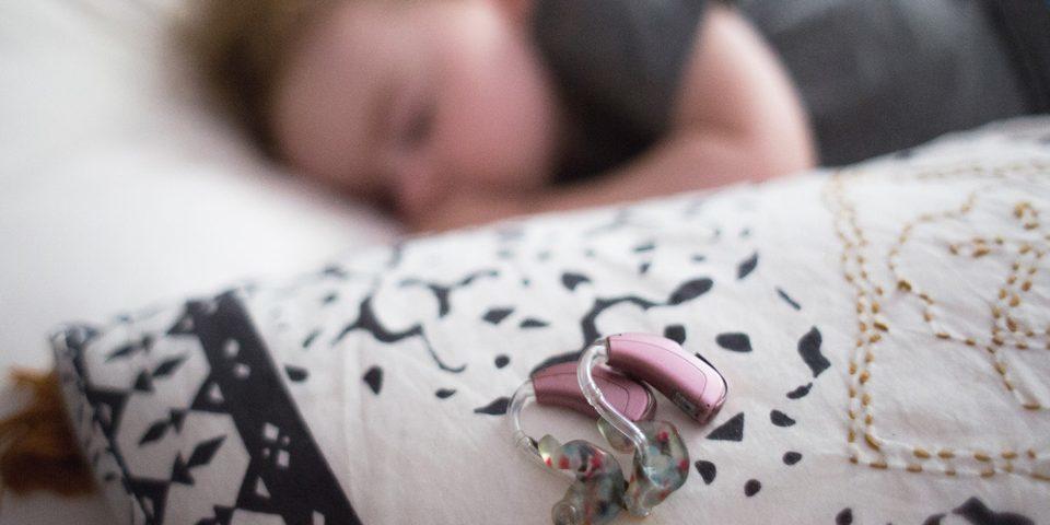 Audífono rosa en la parte superior de la almohada resaltada. Niño dormido de fondo borroso.