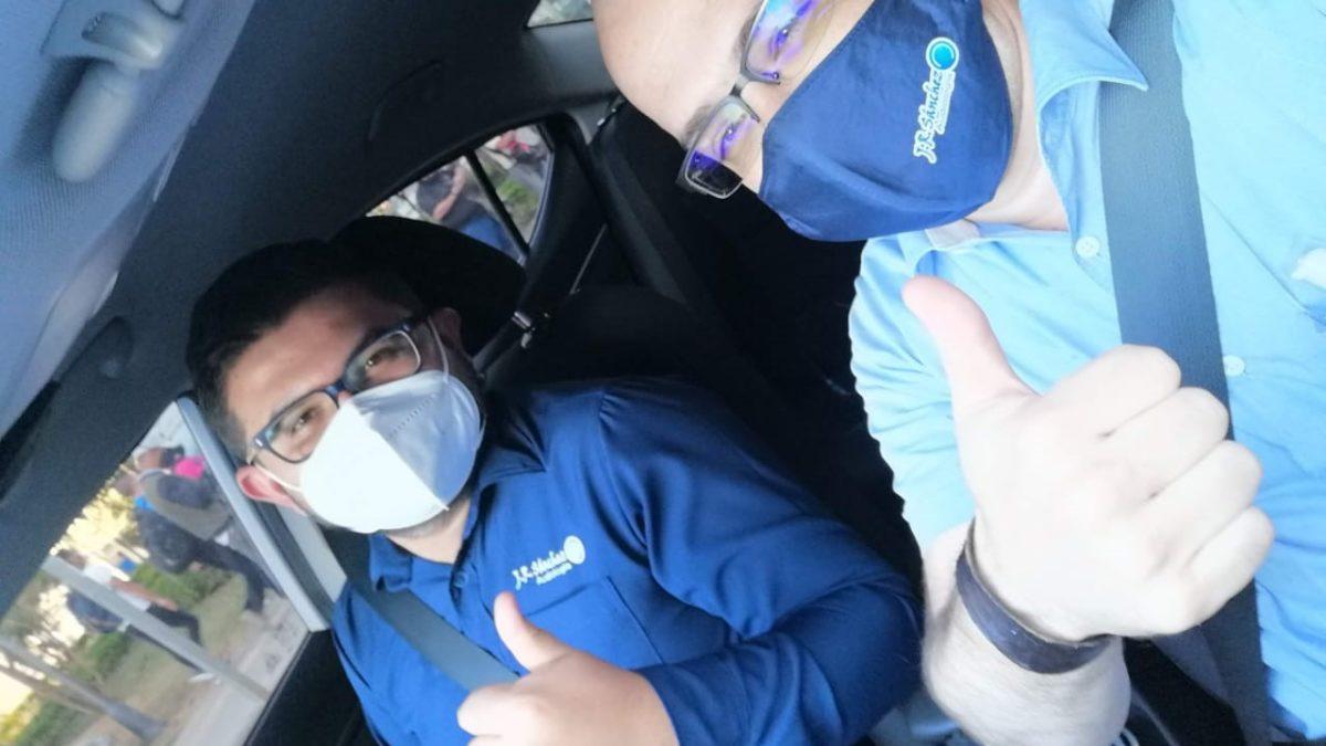 Dos hombres con camisas azules dentro de un automóvil estacionado agitando una foto con un positivo.
