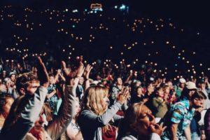 Un lugar cerrado y oscuro, lleno de gente con los brazos en alto. Es un lugar de espectáculos.