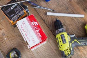 Sobre una mesa de madera hay herramientas que se utilizan en la construcción, como un taladro.