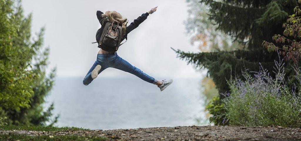 Chica de espaldas a nosotros y saltando en medio de una calle. Ella tiene una mochila en su espalda negra. A su alrededor hay árboles y un mar lejano al fondo.
