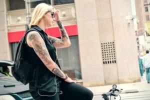 Mujer, con cabello rubio, con tatuajes en su brazo y encima de una bicicleta en una calle