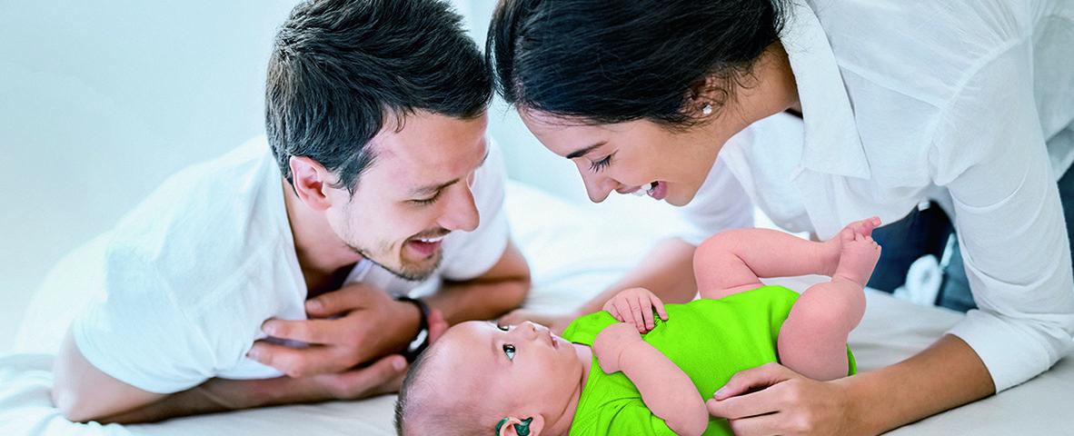 Foreldre leker med spedbarn med hørselstap