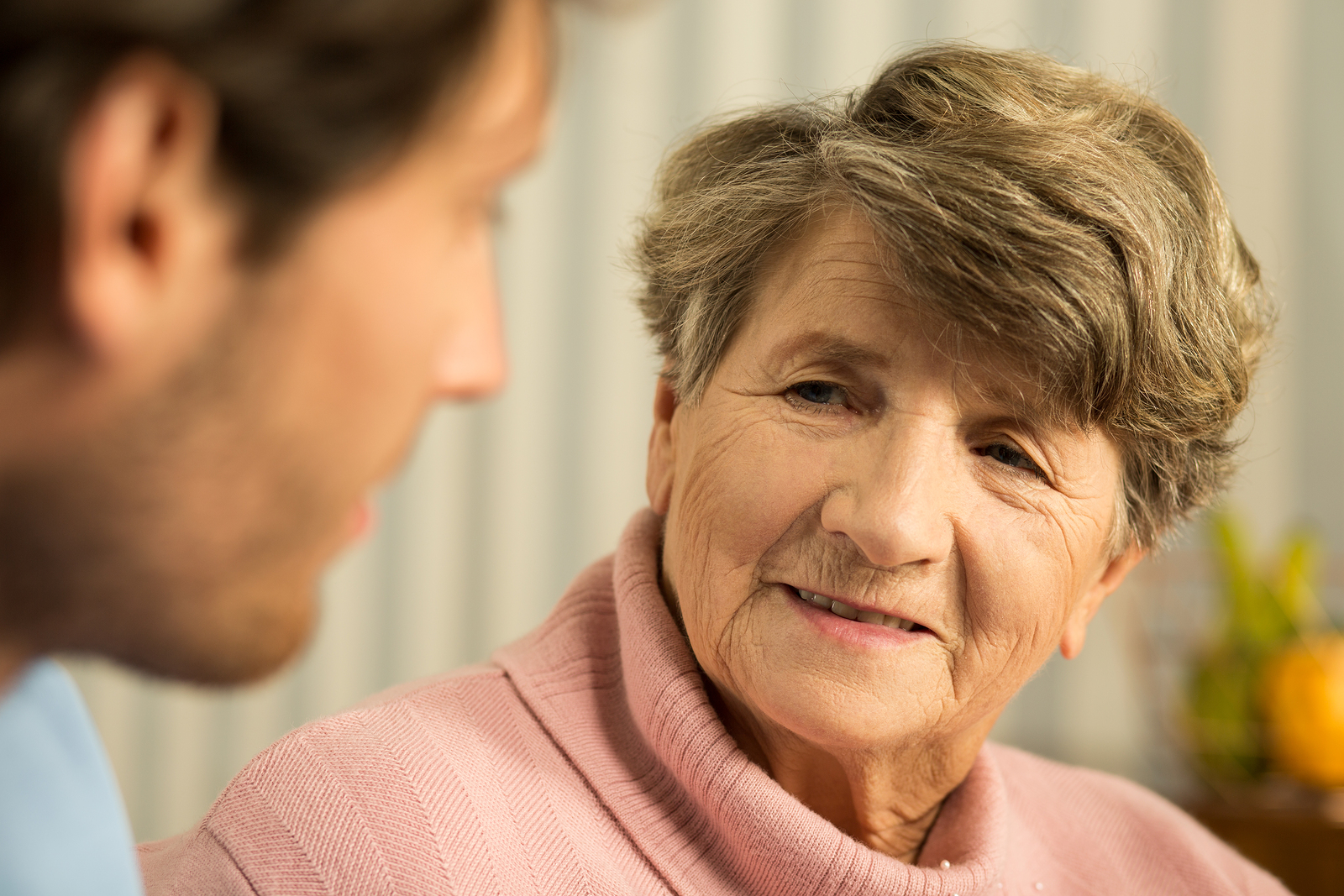 Close-up of senior woman talking with doctor