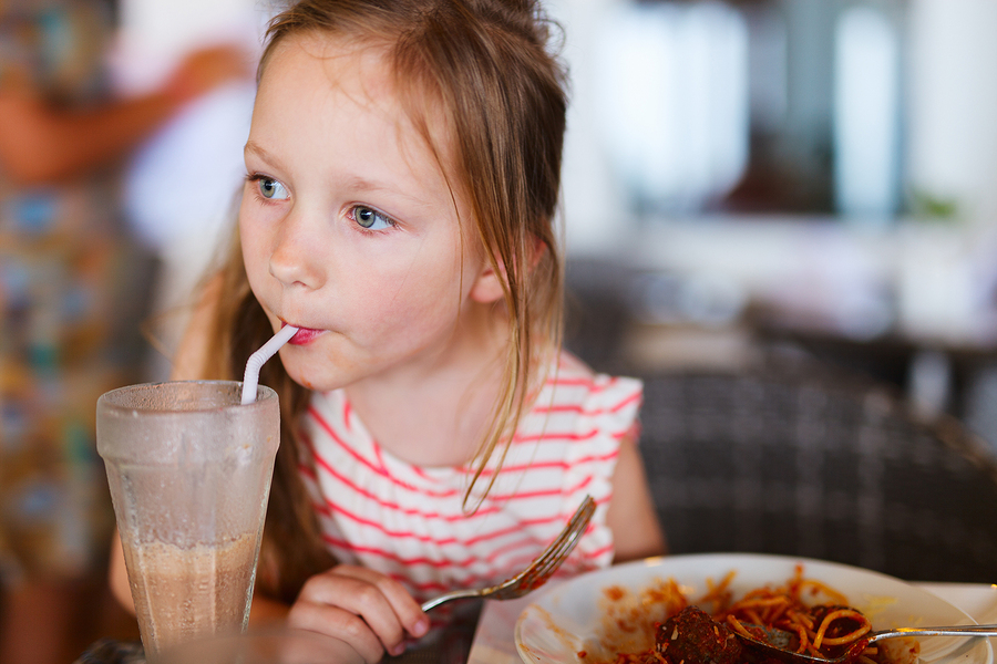 Portrait of adorable little girl having lunch at restaurant